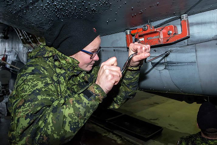 Air Weapons Systems Technician, Aviator Alanna Lasenba removes panel screws on the  CF-188 Hornet aircraft at Mihail Kogalniceanu Air Base, Constanta, Romania during Operation REASSURANCE on November 18, 2017. Photo: Sergeant Daren Kraus. RP14-2017-0126-10