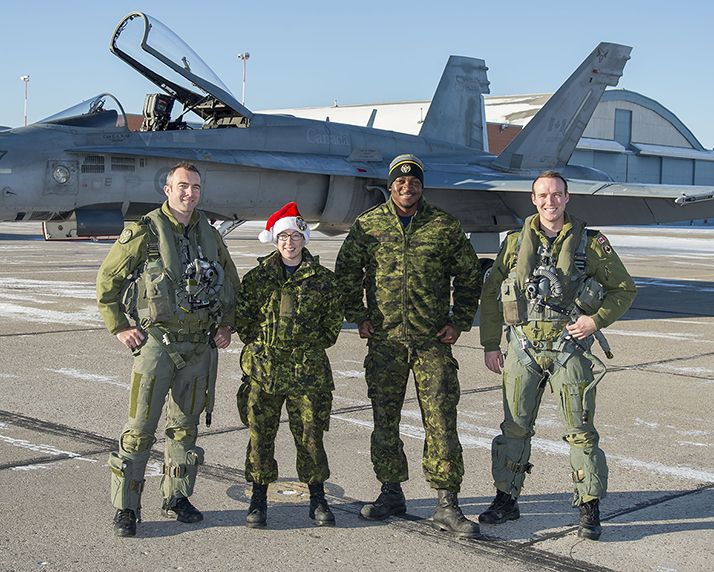 401 Tactical Fighter Squadron members are ready to escort Santa Claus on December 24, 2017. From left to right are Lieutenant-Colonel Forrest Rock, the squadron's commanding officer; Aviator Gillian Lavoie; Corporal Kevin Richmond and Captain Kevin Mittelholtz. PHOTO: Corporal Justin Roy, CK07-2017-1078-005