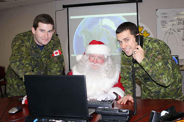 14 Wing Greenwood's Wing Telecommunications Flight technicians hosted Santa Claus on December 8 for his annual briefing on the latest technology he'll need to pull off yet another safe and bug-free Christmas mission. Leading the session were aerospace telecommunication and information systems technician Aviator Jordon Cordona (left) and Captain Cory Richard. PHOTO: Sara White