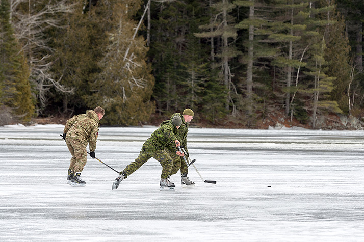 Canadian Army members and a member of the British Army play a friendly game of hockey near Gagetown, New Brunswick on February 6, 2018 while on Exercise ROGUISH BUOY 2018, the Canadian Army's annual combat diving training event. Photo: Cpl Peter Ford, Tactics School, Combat Training Centre (CTC) Gagetown GN33-2018-0053-008