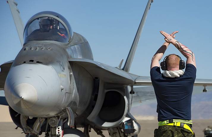 Aviation Systems Technician, Corporal Adam Dore signals a CF-188 Hornet to stop taxiing after a successful training mission during Exercise SANDY FLEECE 2018 being held at Holloman Air Force Base, Alamogordo, New Mexico, USA on February 8, 2018.