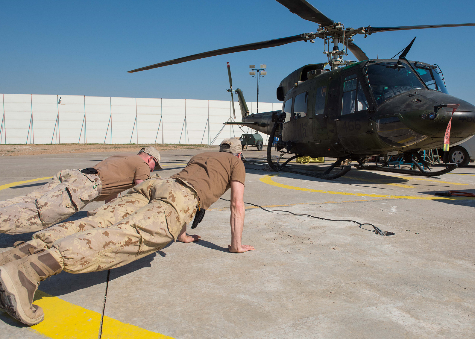 Photo has been digitally altered for OPSEC.  February 21, 2017. Members of Air Task Force – Iraq do pushups by a CH-146 Griffon at Camp Érable during Operation IMPACT on February 21, 2017. (Photo: Op Impact, DND)