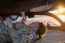 A Canadian Armed Forces Avionics Systems Technician inspects and cleans a CH-146 Griffon helicopter at Camp Érable, Iraq during Operation IMPACT on April 25, 2017.