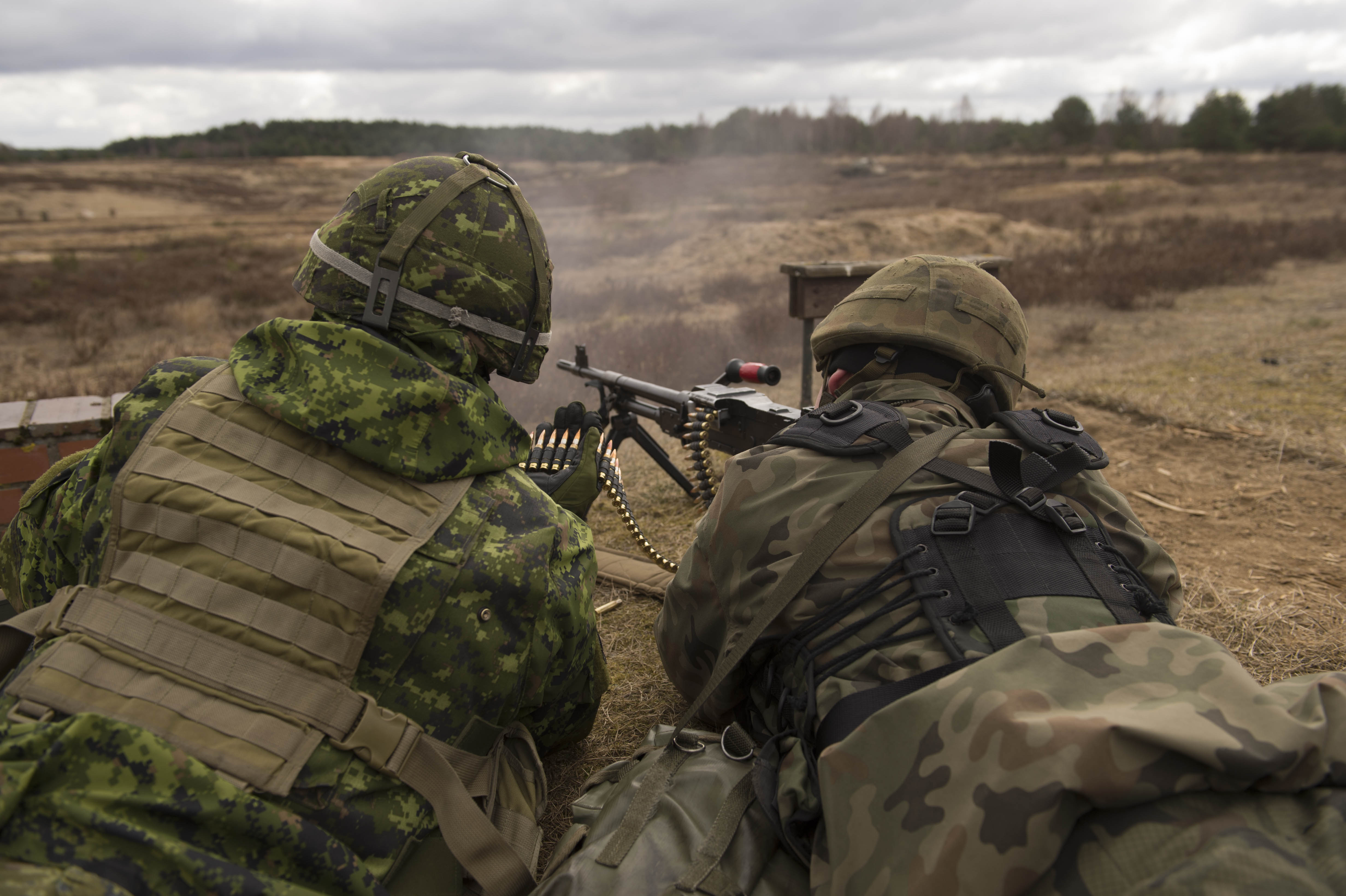 Two soldiers lie side by side on the ground and fire a machine gun